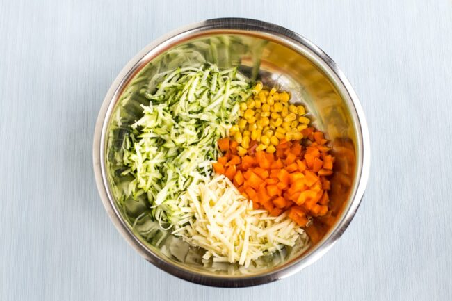 Vegetables and cheese in a mixing bowl.