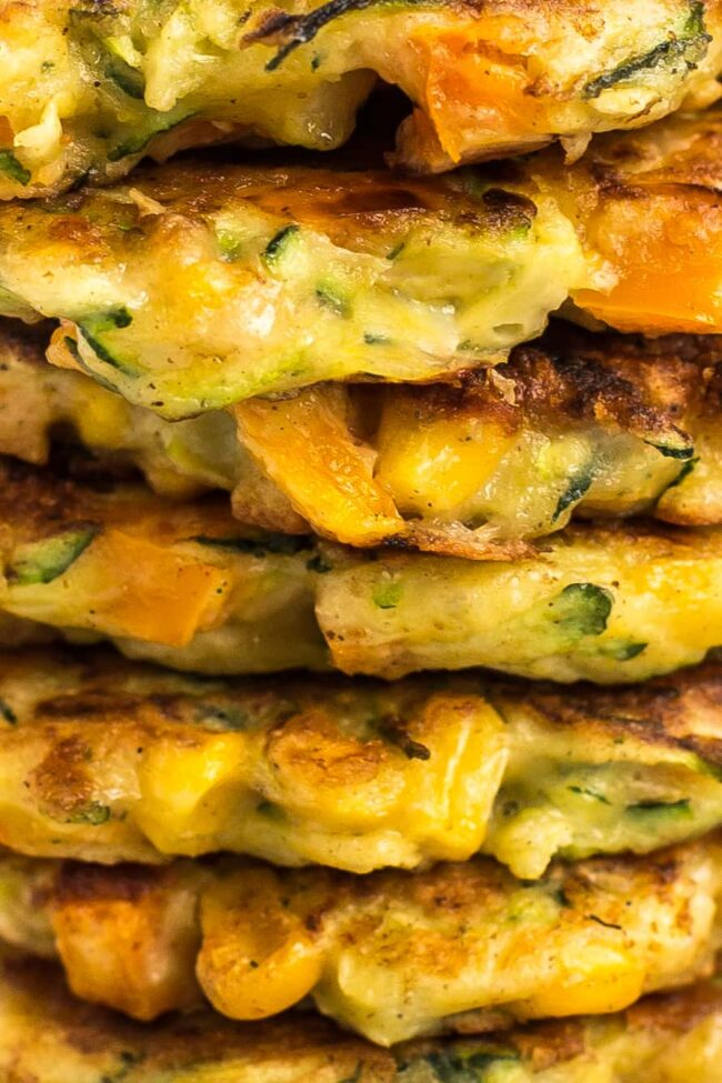 Extreme close up of a stack of cheesy veggie fritters.