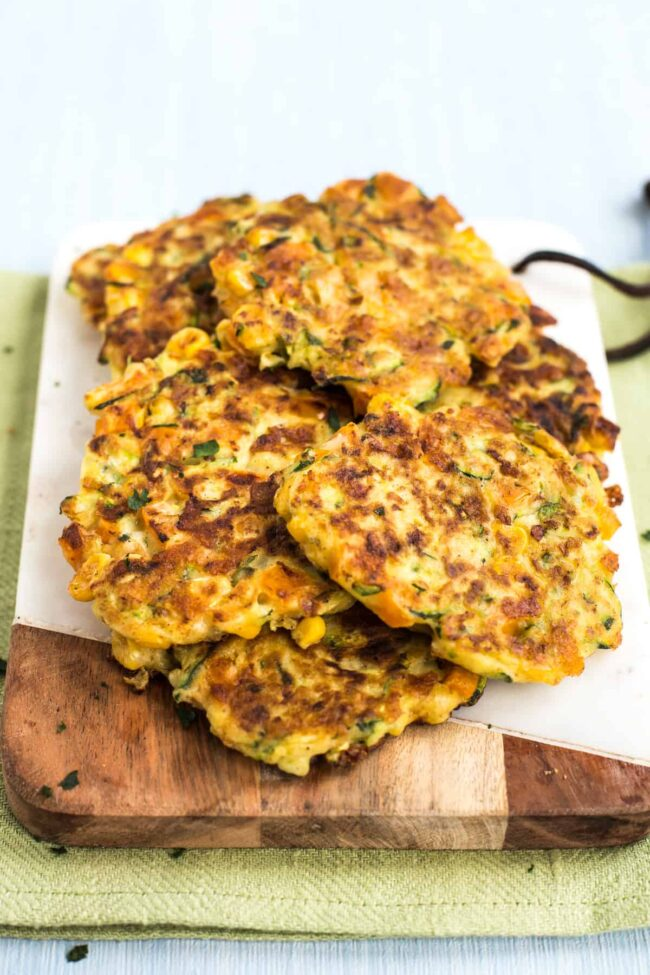 A heap of veggie fritters on a white board.