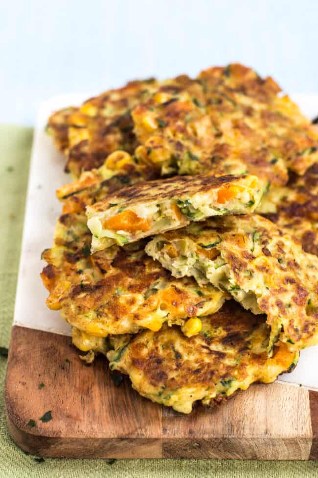 Cheesy veggie fritters in a heap, with one broken in half to see the texture inside.