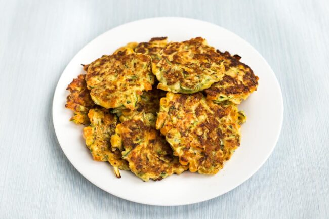 A pile of cheesy veggie fritters on a plate.