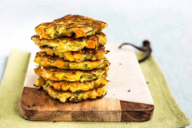 A stack of vegetable fritters on a board.