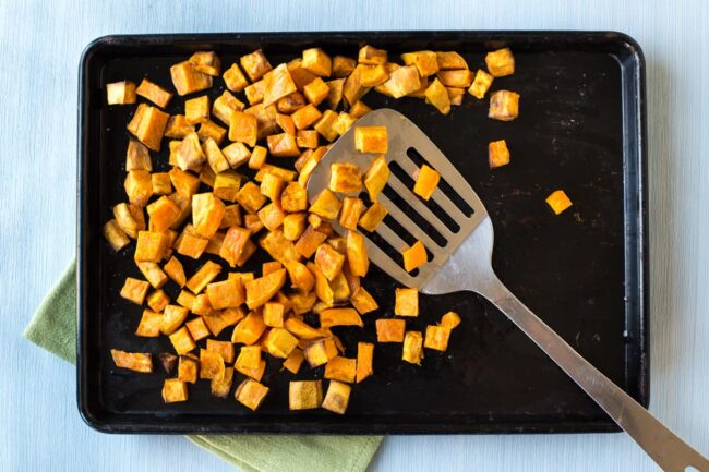 Diced sweet potato roasted on a baking tray with a metal spatula.