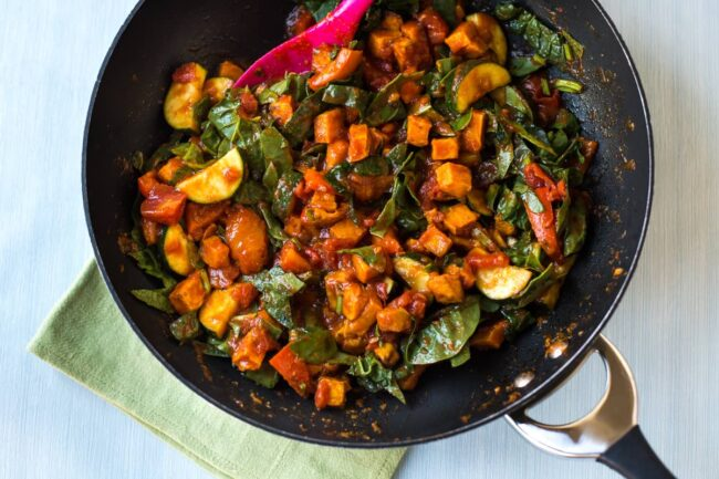 Sweet potato and spinach curry in a wok before being simmered.
