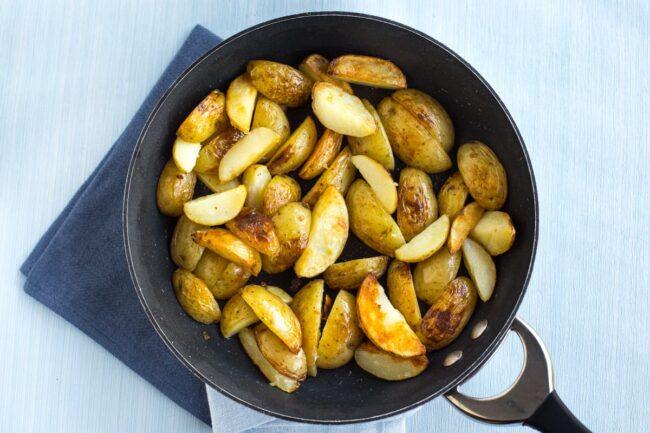 Crispy fried potato wedges in a frying pan.