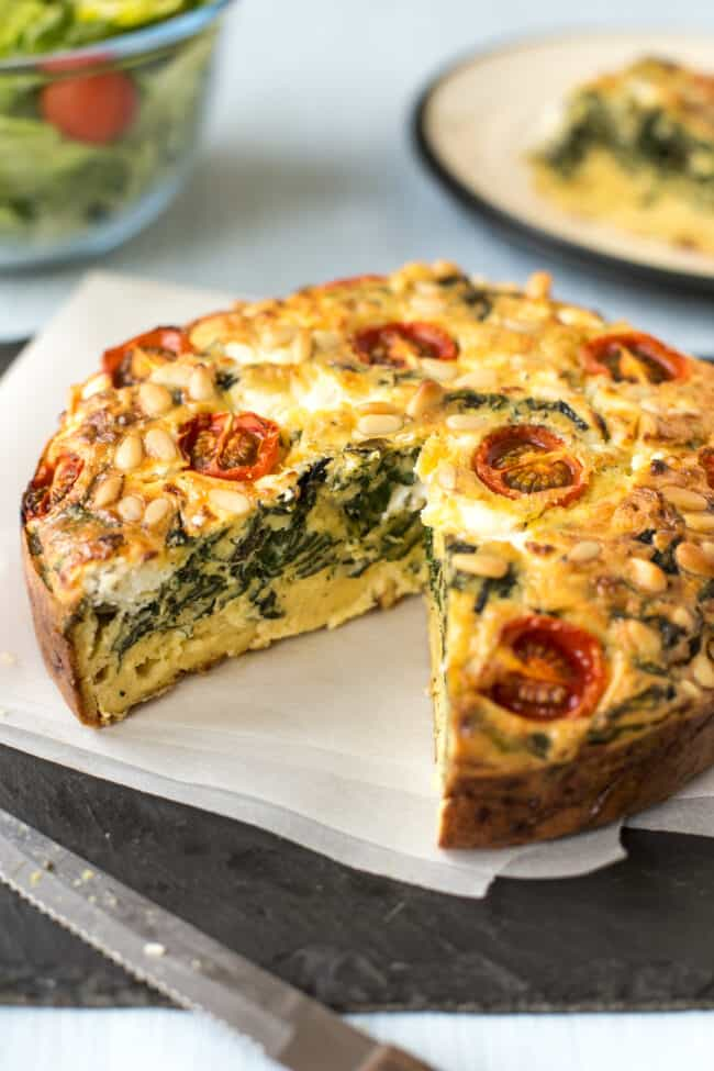 A spinach and tomato quiche with a slice removed.