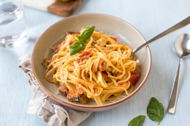 Tomato and mascarpone pasta in a bowl with fresh basil.
