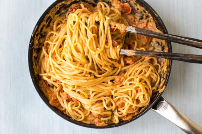 Linguine being tossed through tomato and mascarpone sauce in a frying pan.