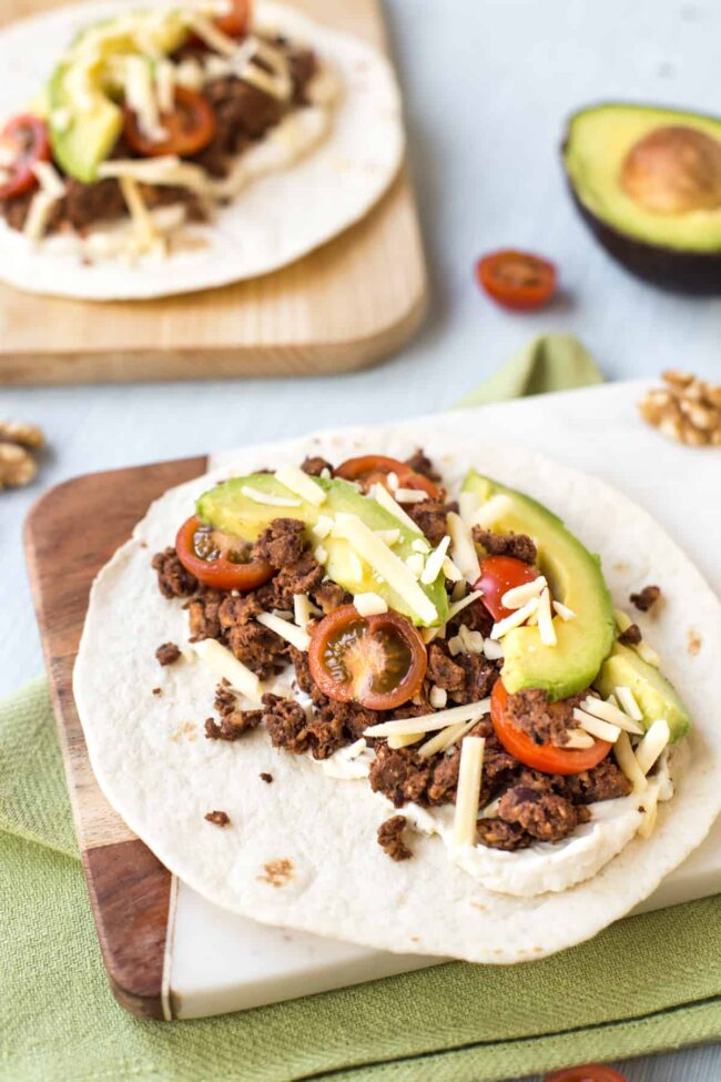 A veggie taco with black bean and walnut taco meat, avocado and tomatoes.