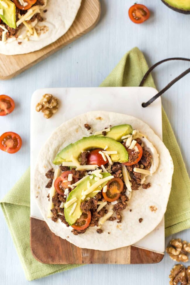 A vegetarian black bean taco topped with avocado and tomatoes.