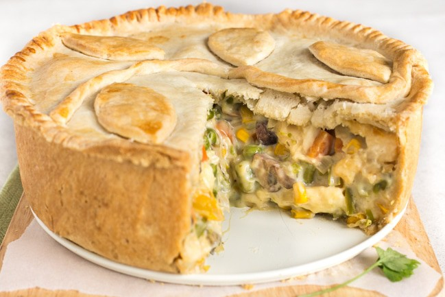 A creamy vegetable and halloumi pie with a slice removed.
