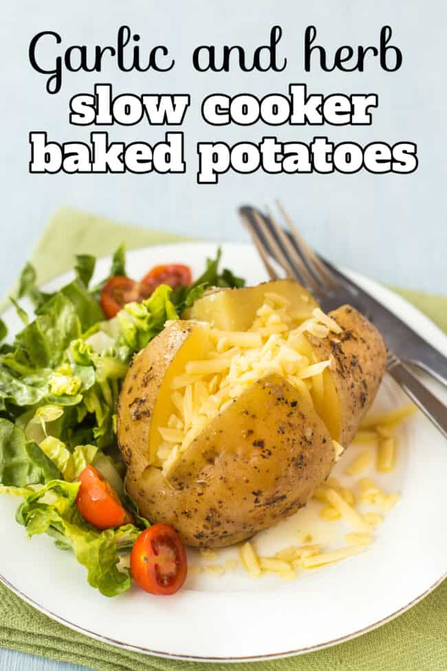 A slow cooker baked potato topped with grated cheese, served with salad.