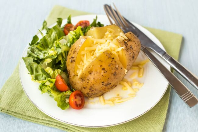 A slow cooker jacket potato on a plate, served with salad.
