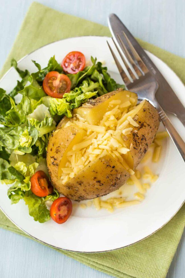 A cheesy jacket potato with salad.