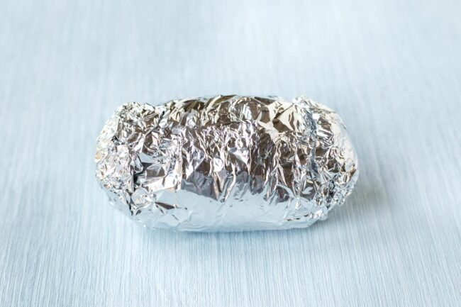 A foil packet containing a potato.