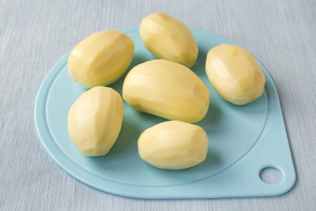 Peeled raw potatoes on a blue chopping board.