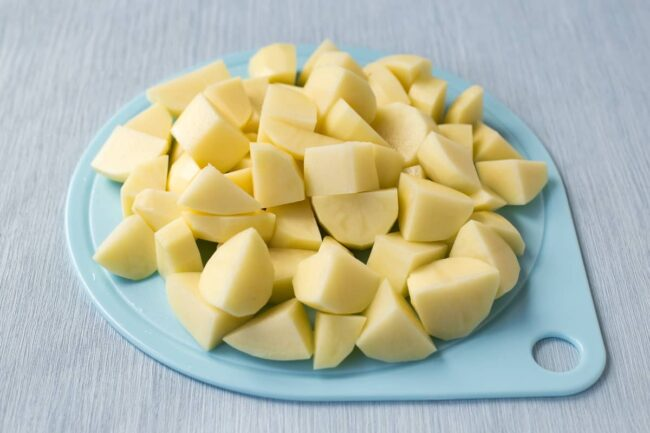 Peeled and chopped raw potatoes on a board.