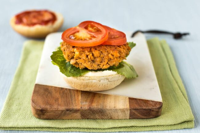 An open-topped vegan chicken burger on a board, topped with sliced tomato.