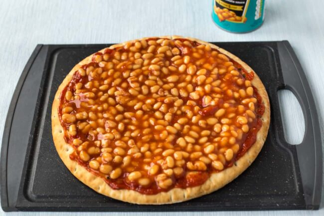 A pizza base topped with tomato sauce and Heinz baked beans.
