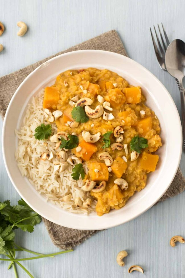 Lentil and sweet potato curry with rice, topped with cashew nuts and cilantro.