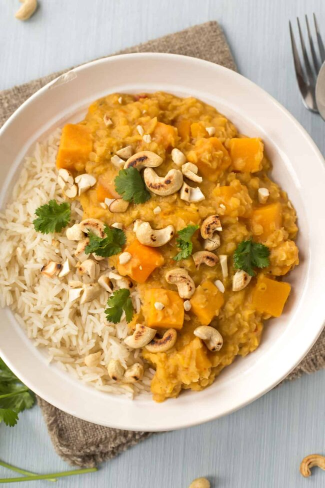 Sweet potato and lentil curry in a bowl topped with toasted cashews and cilantro.