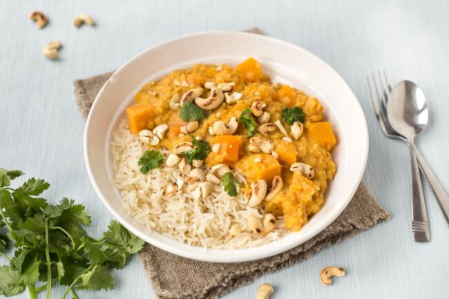 A portion of sweet potato and lentil Thai curry in a bowl with rice.