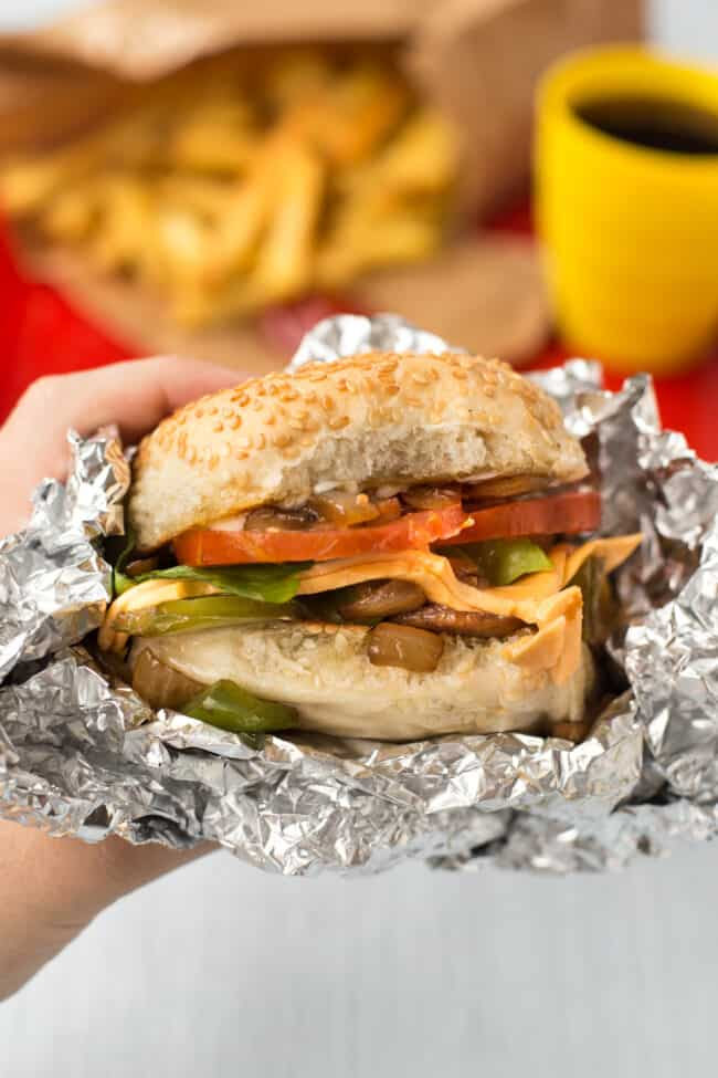 A hand holding up a homemade Five Guys cheese veggie sandwich wrapped in foil.