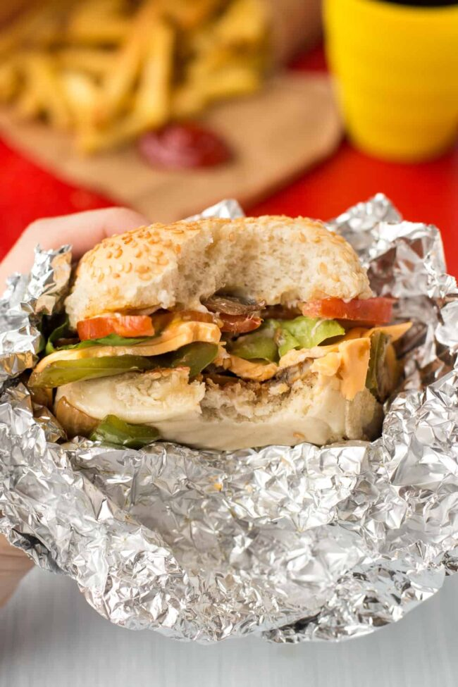 A hand holding up a homemade Five Guys cheese veggie sandwich with a bite taken.
