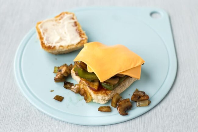 Fried vegetables and cheese piled up on a toasted burger bun.