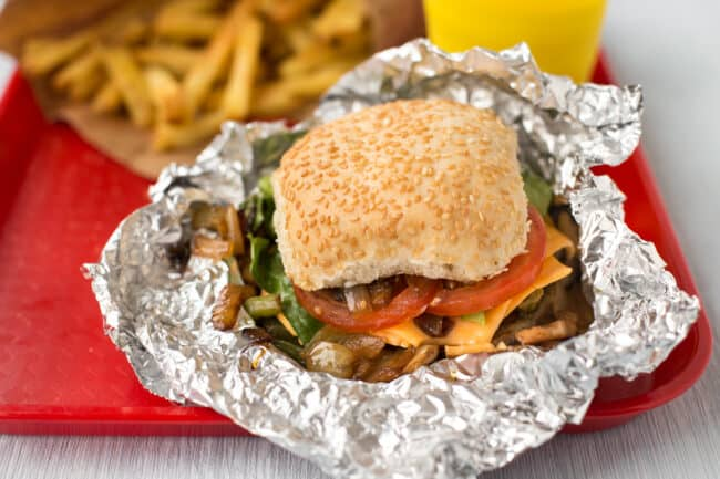A homemade Five Guys cheese veggie sandwich in unwrapped silver foil.