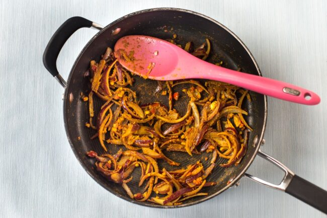 Sliced red onions cooking in a frying pan with spices.