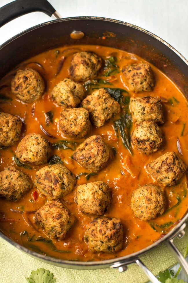 Crispy falafel sitting in a pan of curry sauce.