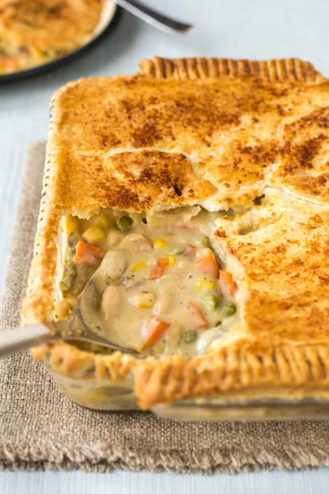 A puff pastry topped pie with cheesy vegetables showing underneath.
