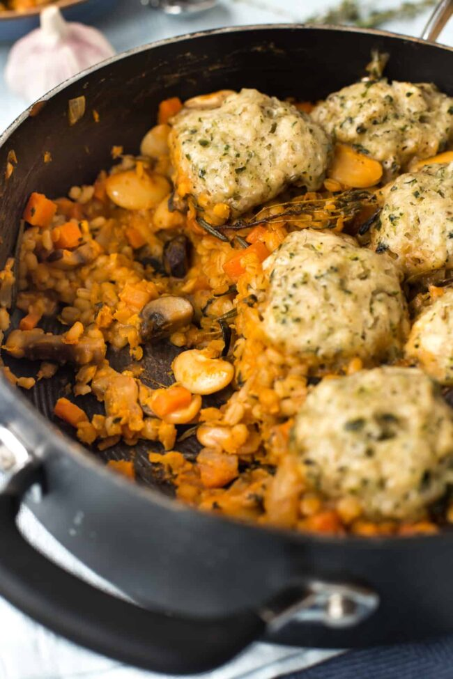 Vegan cassoulet in a pan topped with herbed dumplings.