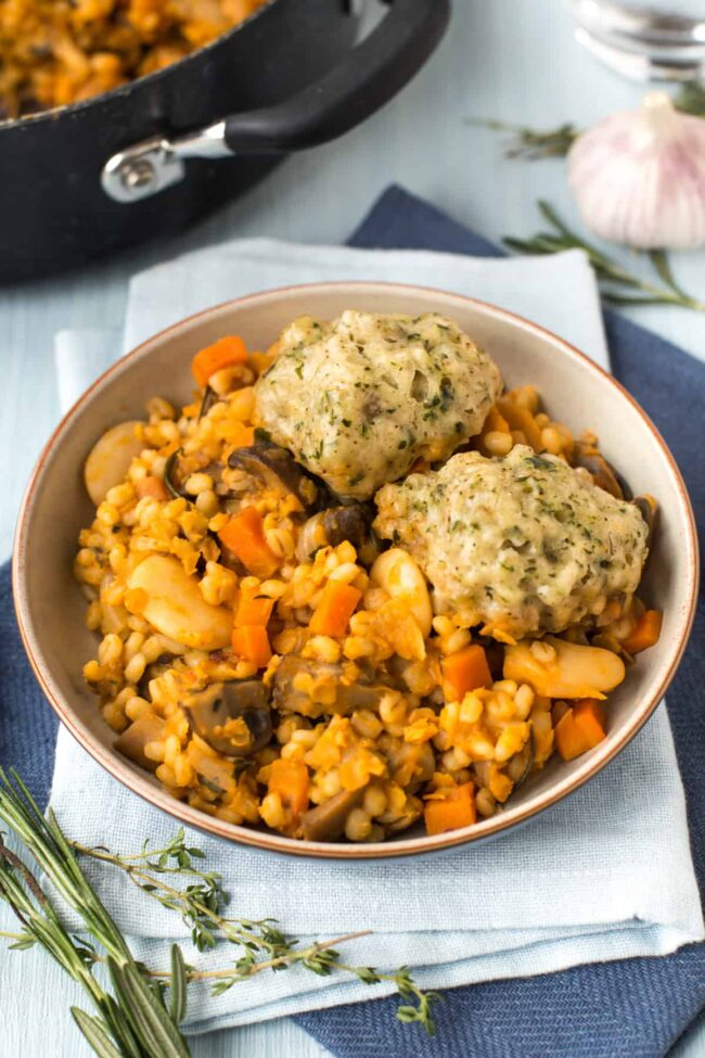 Bowlful of vegan cassoulet with herby dumplings, beans and pearl barley.