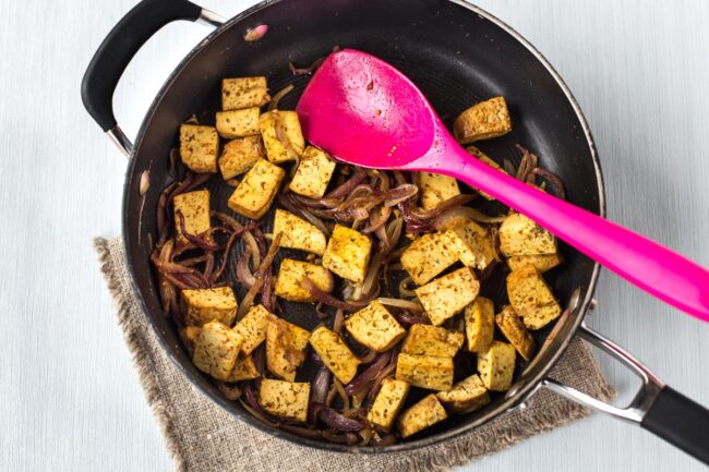Smoked tofu and red onion cooking in a frying pan.