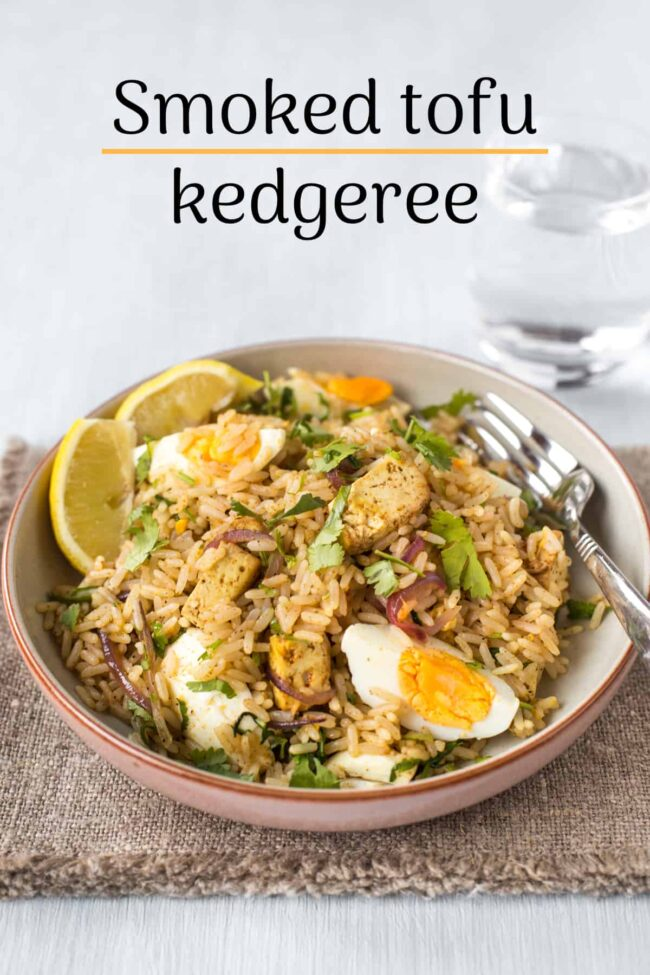 Portion of tofu kedgeree in a bowl with lemon and parsley.