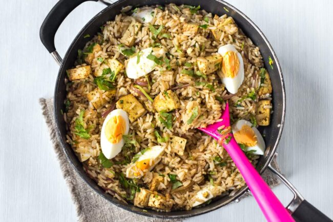 Vegetarian kedgeree in a pan with boiled eggs and tofu.