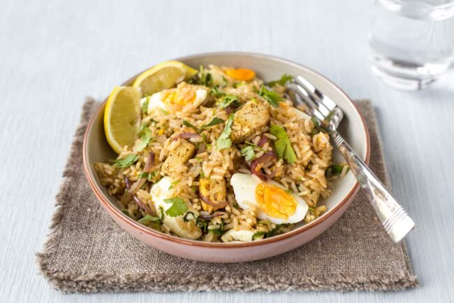 Portion of tofu kedgeree in a bowl with slices of boiled egg and parsley.