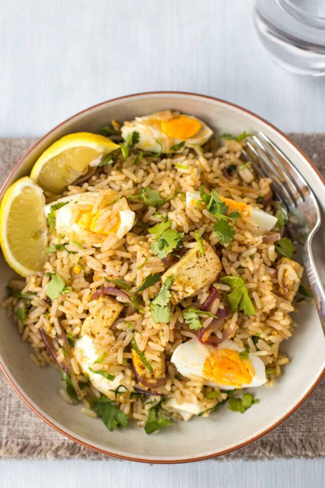 A portion of vegetarian kedgeree with smoked tofu and boiled eggs.