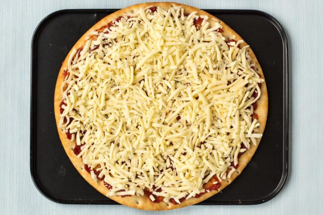 An uncooked cheese and tomato pizza on a baking tray.