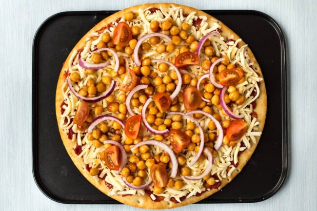 An uncooked pizza topped with BBQ chickpeas, red onion and cherry tomatoes.