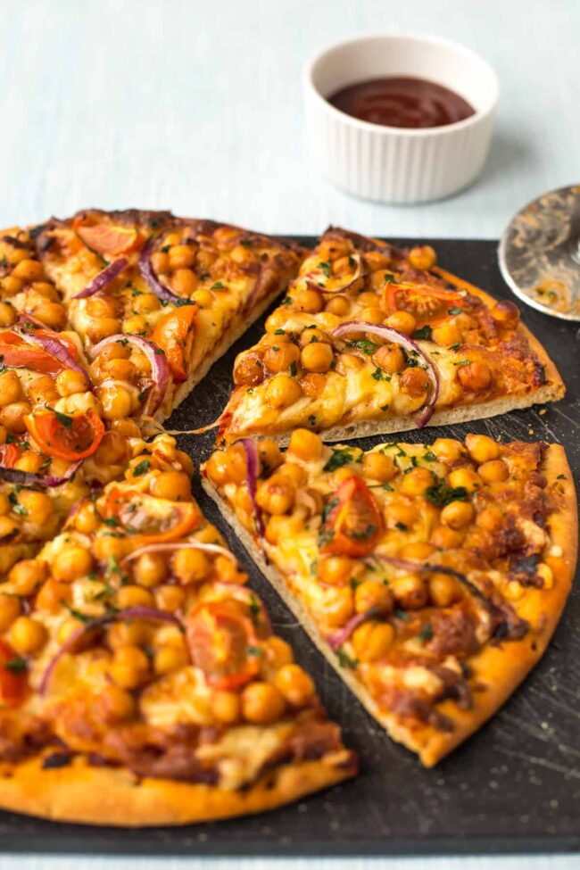A BBQ chickpea pizza cut into slices on a board.