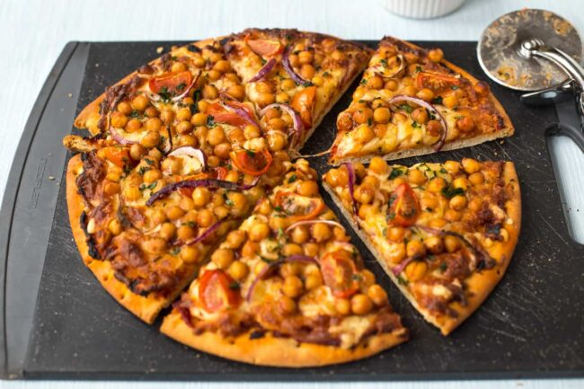 A BBQ chickpea pizza cut into slices on a chopping board.