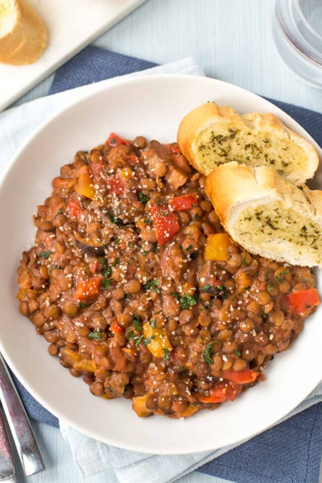 A portion of cheesy lentils with garlic bread.
