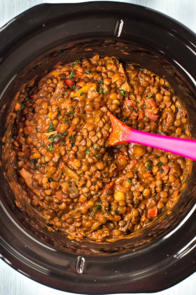 Cheesy lentils and vegetables in a slow cooker pot.