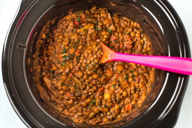 Cheesy lentils in a slow cooker pot.