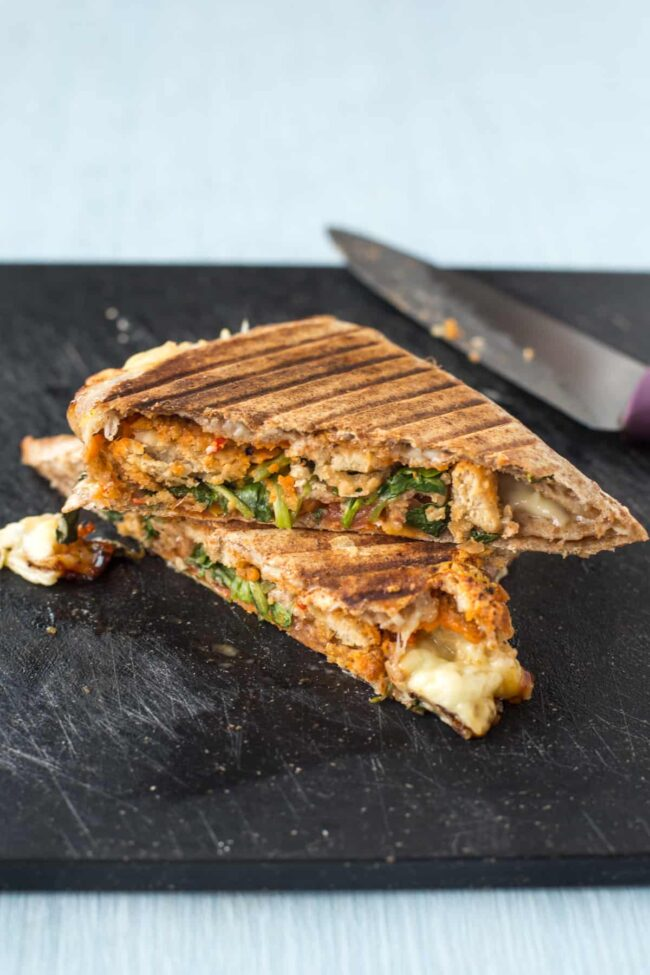 A grilled tortilla cut in half, stuffed with vegetarian nuggets and watercress.