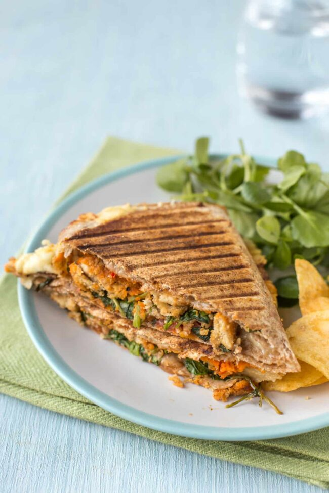 A stuffed tortilla wrap on a plate with watercress and crisps.