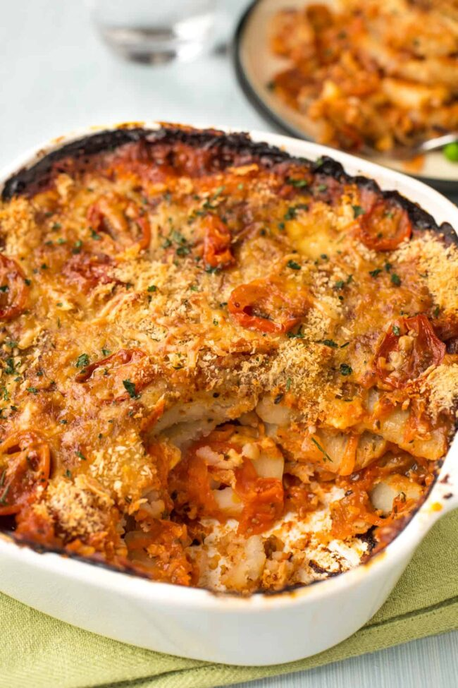 Cheese and tomato potato bake in a dish with a crispy topping.